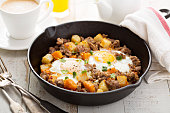Potato and sweet potato hash with eggs in cast iron pan