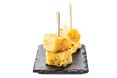 Spanish tapas. Tortilla de patatas toothpick isolated on white backround.
