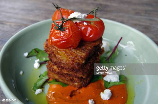 Potato rosti served with roasted tomatoes and crumbled feta cheese on a wooden table