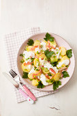 Potato salad garnished with spring onions, parsley and mayonnaise, close up