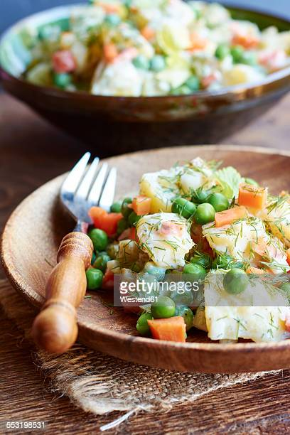 Potato salad with potatoes, carrots, peas, onions, soy yogurt, pickles and dill