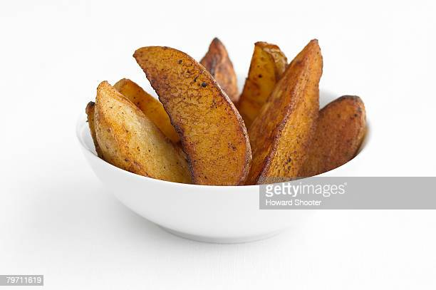 Potato wedges in a white bowl, studio shot