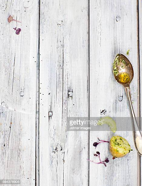 Potatoes and spoon on wooden surface