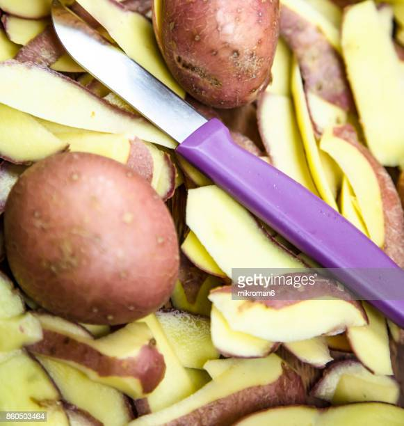 Potatoes, whole and peeled on a wooden board