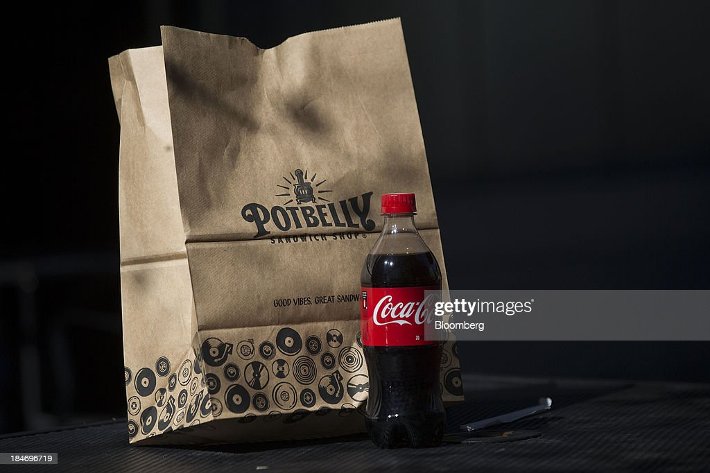 A Potbelly Corp. bag and a bottle of Coca-Cola Co. soda sit on a table outside a Potbelly Sandwich Shop in Washington, D.C., U.S., on Tuesday, Oct. 15, 2013. Potbelly Corp., the Chicago-based purveyor of made-to-order toasted sandwiches, held its initial public offering (IPO) on Oct. 4. Photographer: Andrew Harrer/Bloomberg via Getty Images