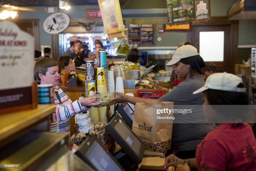 A Potbelly Corp. employee hands a customer her order at a Potbelly Sandwich Shop in Washington, D.C., U.S., on Tuesday, Oct. 15, 2013. Potbelly Corp., the Chicago-based purveyor of made-to-order toasted sandwiches, held its initial public offering (IPO) on Oct. 4. Photographer: Andrew Harrer/Bloomberg via Getty Images