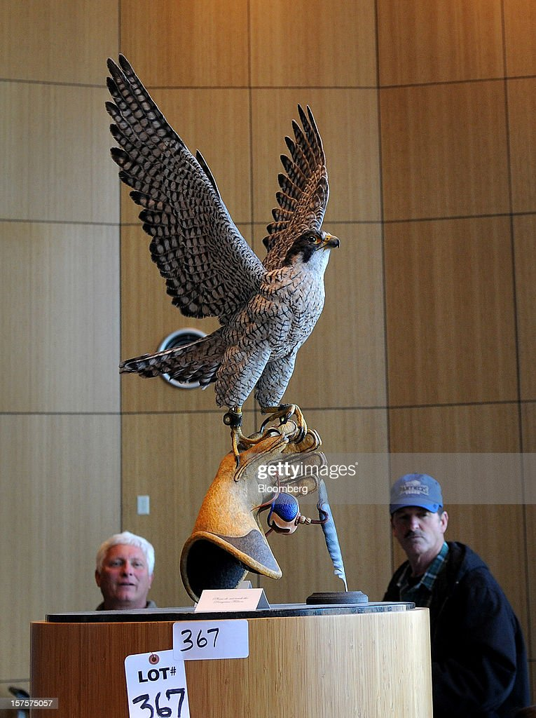 Potential bidders look over a Peregrine Falcon statue computers and monitors during an auction preview at the former Peregrine Financial Group Inc. offices in Cedar Rapids, Iowa, U.S., on Tuesday, Dec. 4, 2012. Assets belonging to Russell Wasendorf Sr., founder of the bankrupt commodities firm Peregrine Financial Group Inc., are scheduled to be auctioned off on Dec. 5. Photographer: Steve Pope/Bloomberg via Getty Images