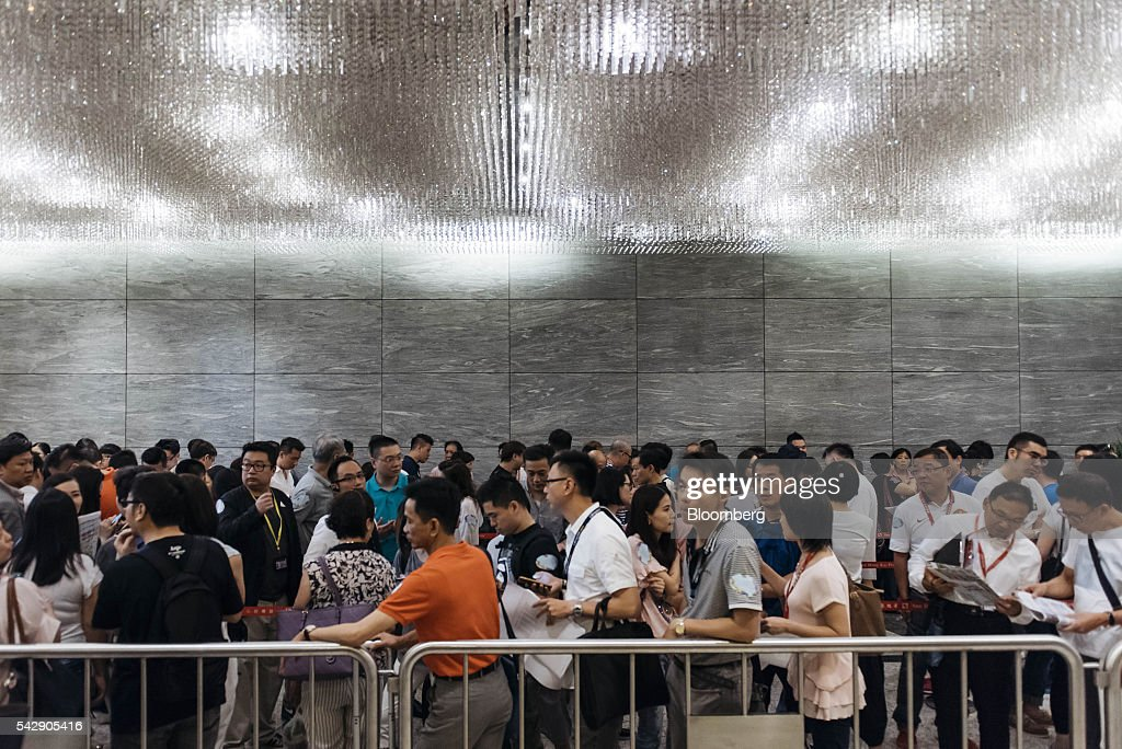 Potential buyers and real estate agents stand in line outside the sales office of Park Yoho Venezia, a residential property developed by Sun Hung Kai Properties Ltd., in Hong Kong, China, on Saturday, June 25, 2016. Sun Hung Kai, Hong Kong's largest developer by market value, is offering mortgages worth as much as 120 percent of a home's value at one of its projects as sales have slumped in the city. Photographer: Anthony Kwan/Bloomberg via Getty Images