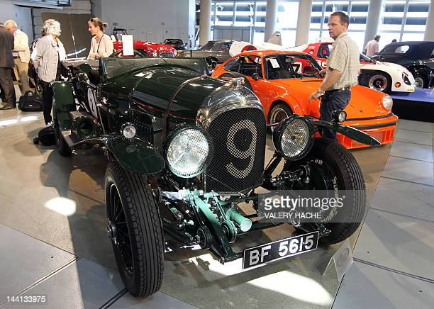 Potential buyers and visitors gather around the 1925 Bentley 4 1/2 litre Le Mans Replica Tourer at the Grimaldi Forum in Monaco on May 10 on the eve...
