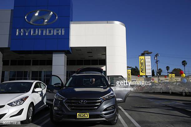 A potential car buyer views the trunk of a Hyundai Motor Co Tuscon compact sports utility vehicle on the lot of the Keyes Hyundai dealership in the...