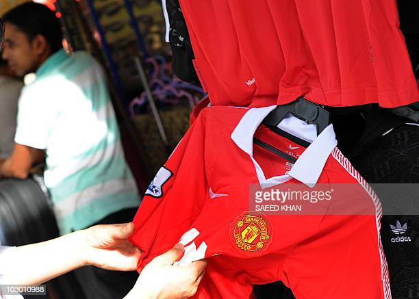 A potential customer checks the quality of Manchester United football team jersey at a roadside shop in down town in Kuala Lumpur on July 21 2010...