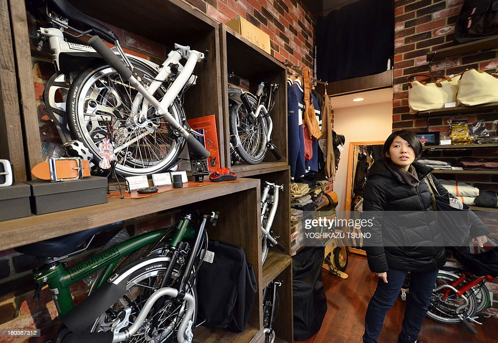 A potential customer looks at a selection of Brompton folding bicycles in a shop in Yokohama, in Japan, on January 27, 2013. British bicycle company Brompton produced 36,000 bikes in 2012 with a turnover of around GBP 20m (approx 23.25m euros). Brompton's folding bikes have proved popular with customers in Asian countries such as Japan. AFP PHOTO / Yoshikazu TSUNO