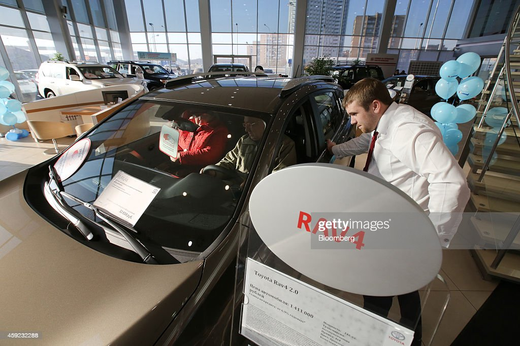 Potential customers check out the interior of a Toyota Rav 4 vehicle while a salesman looks on in the showroom of a Toyota Motor Corp automobile...