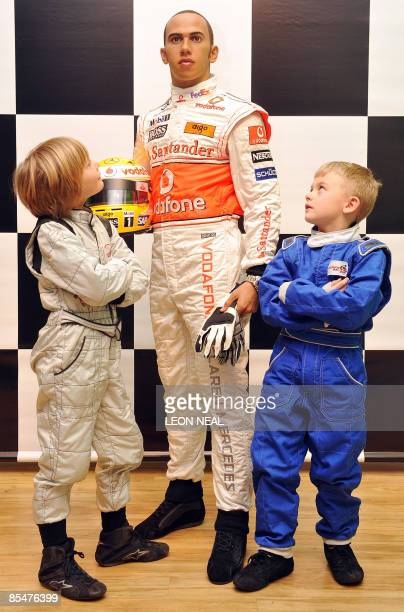 Potential future motor racing champions Billy Monger and Myles Apps stand with a wax figure of British Formula One world champion Lewis Hamilton at...