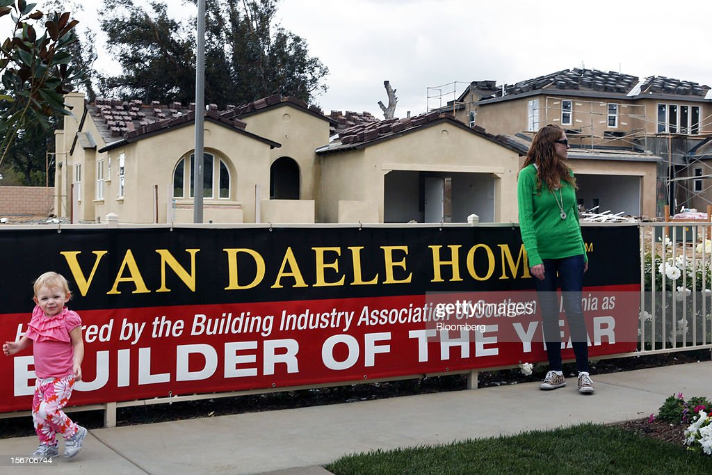 Potential house buyer Kristina Coughlin, right, and daughter Haylee Coughlin, 2, walk past homes under construction at the Van Daele Estates at Etiwanda development in Rancho Cucamonga, California, U.S., on Sunday, Nov. 18, 2012. The U.S. Census Bureau is scheduled to release housing starts figures on Nov. 20. Photographer: Patrick T. Fallon/Bloomberg via Getty Images