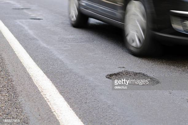 Pothole on the road next to a driving car