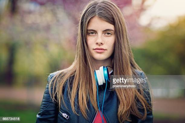 Potrait of a beautiful teen girl standing at the front of blossom tree