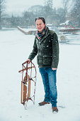 Mature man is smiling for the camera while standing outdoors in the snow, holding a sleigh.