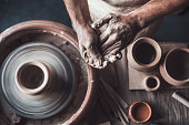 Top view of potter standing near pottery wheel and holding hands together