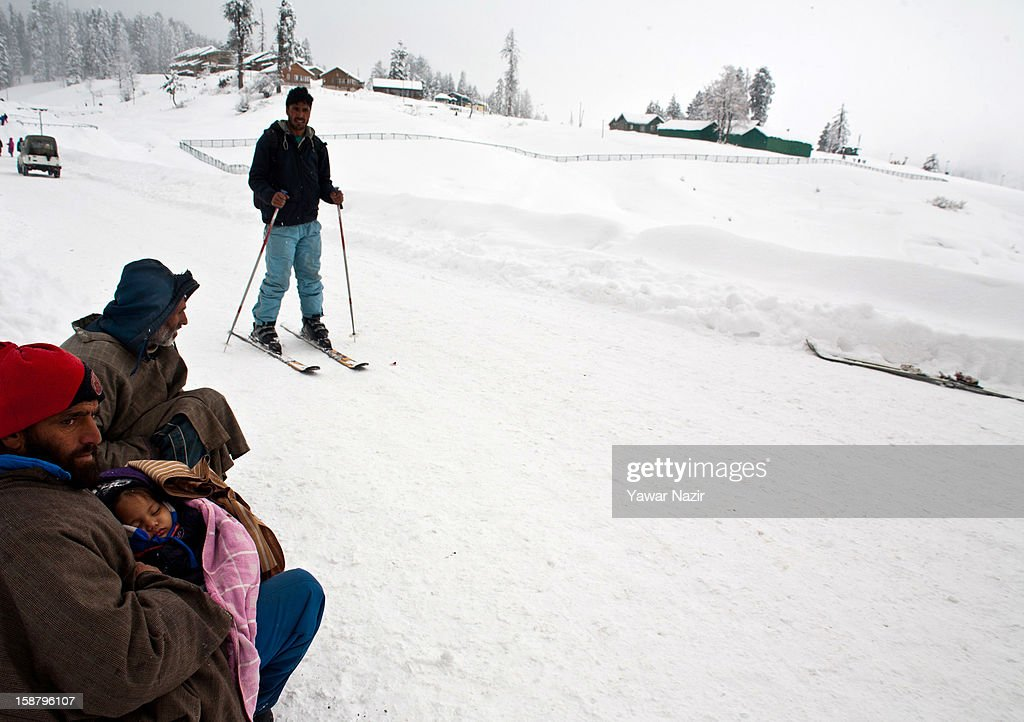 A potter carries the child of a tourist as he sits on a road after a snowfall on December 29, 2012 in Gulmarg, 54 km (35 miles) to the west of Srinagar, the summer capital of Indian-administered Kashmir, India. With the second round of heavy snowfall in Kashmir valley, skiers from around the globe have descended on the ski resort of Gulmarg, known for long-run skiing, snow-boarding, heli-skiing and steep mountains. Gulmarg is located less than six miles from the ceasefire line or Line of Control (LoC) that divides Kashmir between India and Pakistan. As a sense of normalcy has started to return to this strife-torn region, various foreign governments, including the United Kingdom, have lifted the travel advisory to its citizens traveling to Kashmir, raising the hopes of the local tourism industry, officials said.