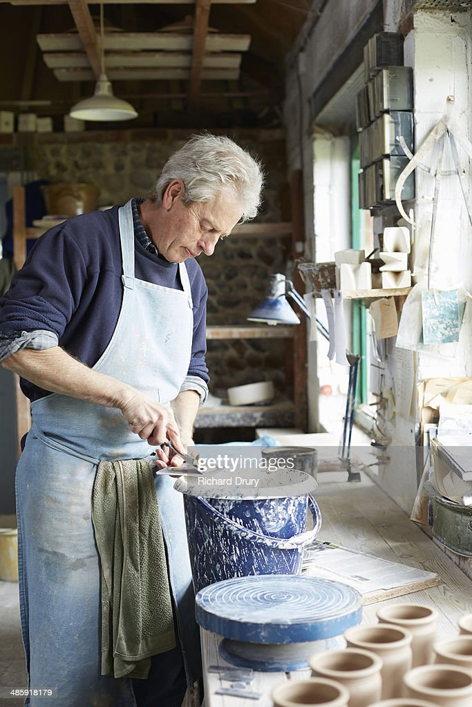 Potter cleaning throwing batts : Stock Photo