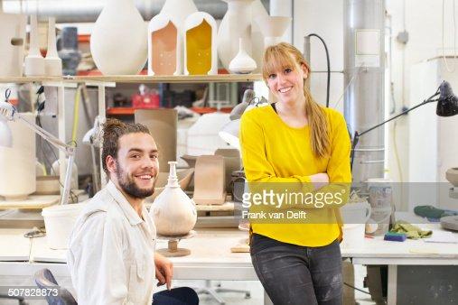 Potter couple posing in ceramic workshop