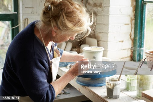 Potter decorating small pot with coloured glazes