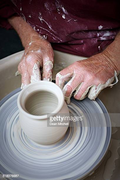 Potter hands making a pot on pottery wheel
