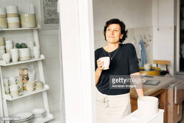 Potter holding coffee cup