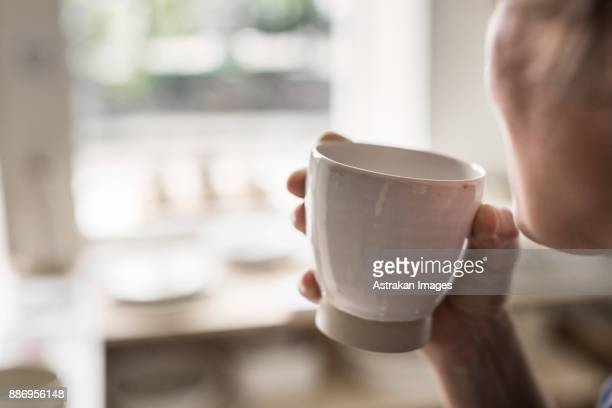 Potter holding cup
