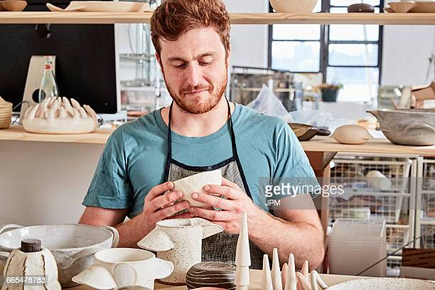 Potter in workshop looking at pottery