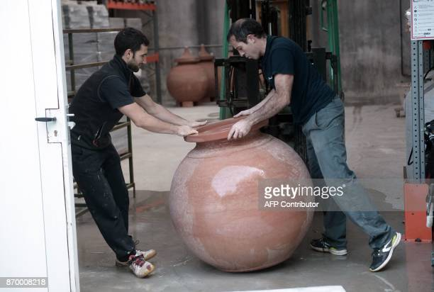 Potter Inaki Goicoechea and an employee move a 'dolia' earthenware jar to be used to age wine on October 12 at his workshop in Osses southwestern...