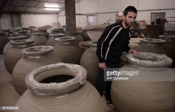 Potter Inaki Goicoechea inspects 'dolia' earthenware jars to be used to age wine on October 12 at his workshop in Osses southwestern France The...
