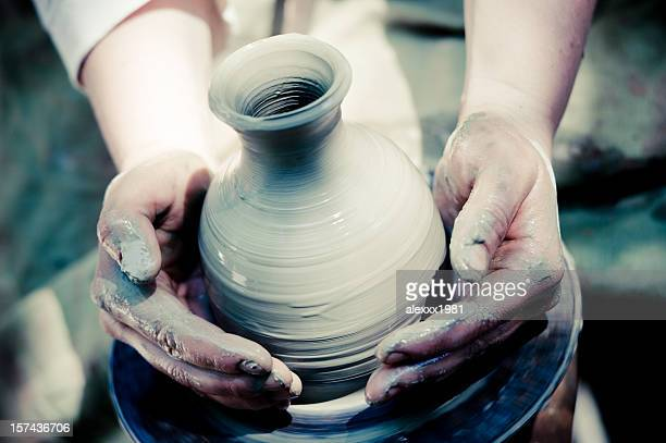 potter makes a jug out of clay