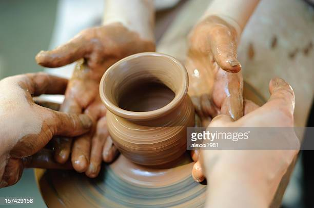 Potter making a jug out of clay on a pottery wheel