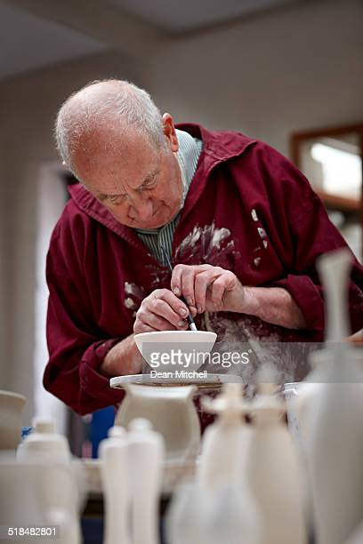 Potter painting a clay pot