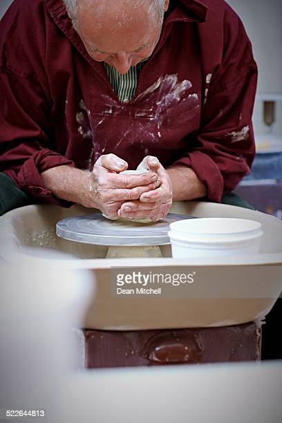 Potter placing clay on pottery wheel