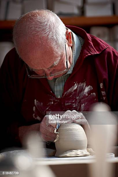 Potter shaping a jar base on spinning wheel