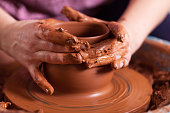 Potter shaping clay on the pottery wheel