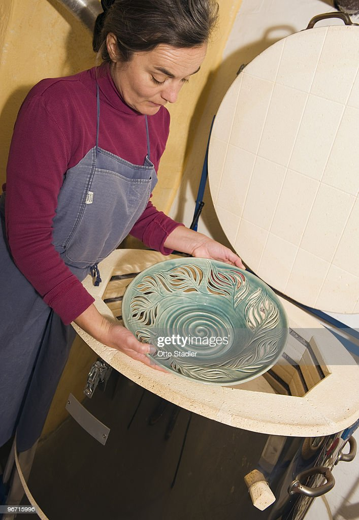 Potter takes ready burned Ceramicware out of Kiln : Stock Photo