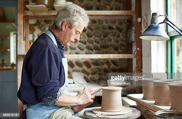 Potter turning the footring of a cutlery drainer