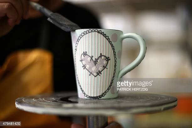 A pottery worker decorates a mug in a pottery workshop in Soufflenheim eastern France on June 30 2015 AFP PHOTO / PATRICK HERTZOG