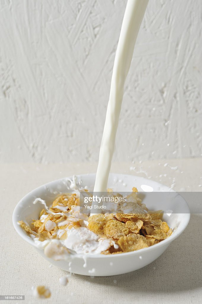 Pour the milk into cereal : Stock Photo