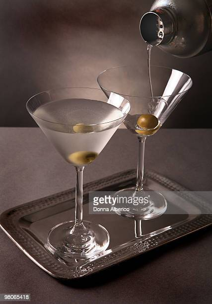 pouring a vodka martini with olive