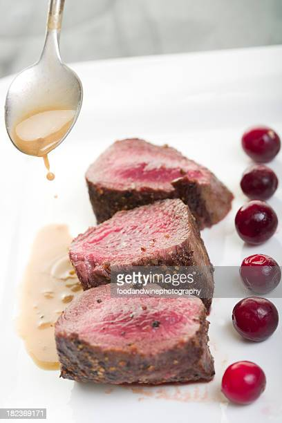 Pouring au jus on a plate of venison steaks