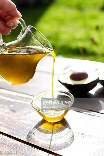 Pouring avocado oil into glass bowl