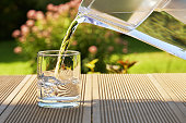 Pouring clear filtered water from a water filtration jug into a glass on the green summer garden background in a warm sunny summer day