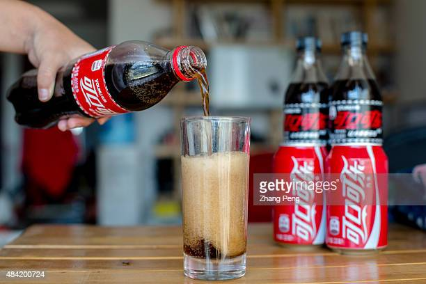 Pouring Coca Cola into a glass on a dining table The strong dollar hit CocaColas overseas operations particularly in China