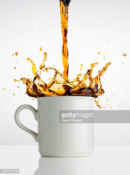 Pouring coffee into cup with splash