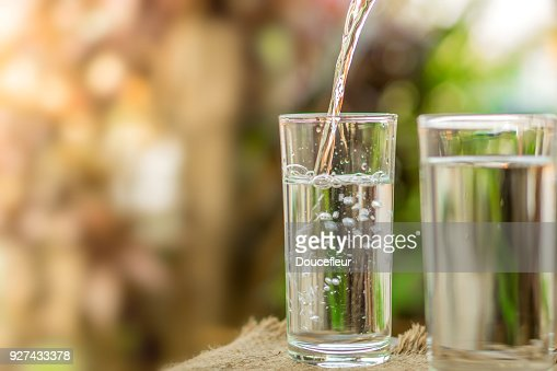 Pouring fresh water on drinking glass over nature sunlight morning background : Foto de stock